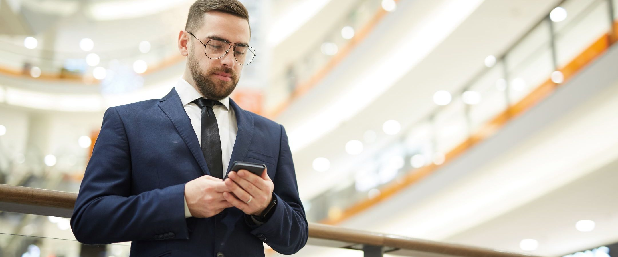 Young bearded businessman in elegant suit scrolling in smartphone or texting inside modern trade center